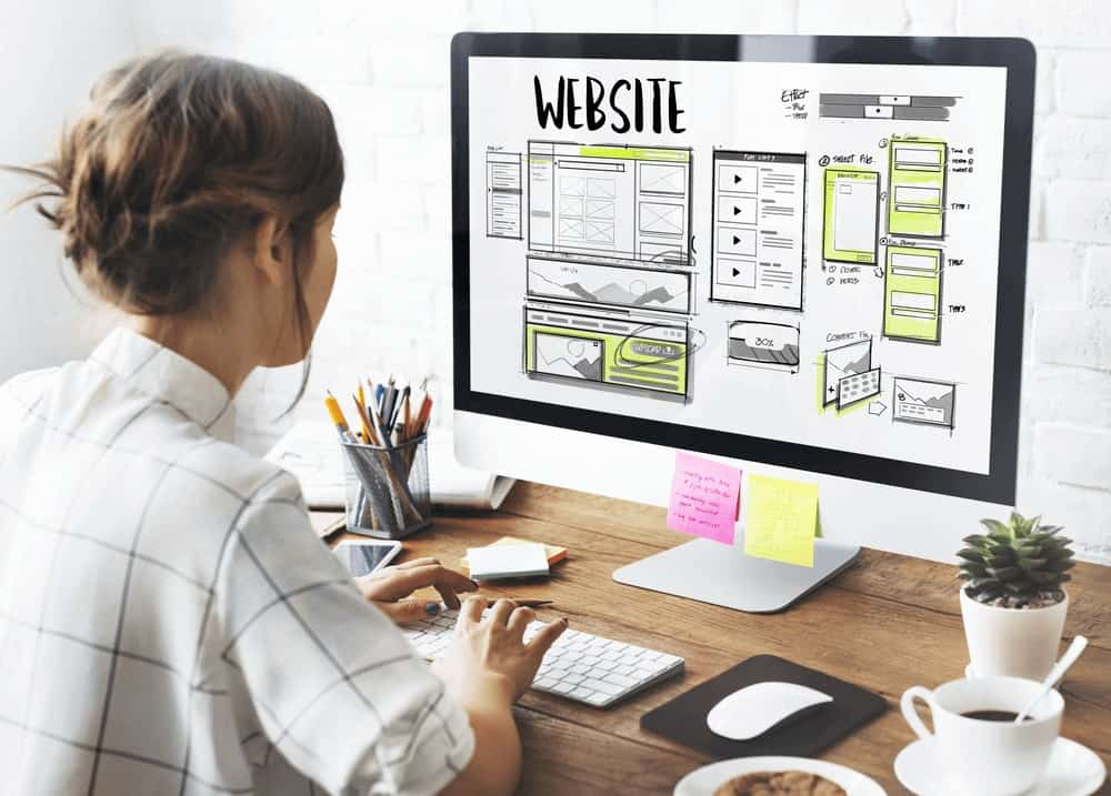 Web design being planned on computer by female worker sitting at desk